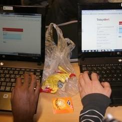 Två händer vilar på två datorer som står bredvid varandra och det ligger godispapper mellan datorern