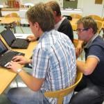 Man hukar sig ner bakom två män som sitter med datorer.