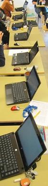 Flera datorer står på rad på skolbänk.