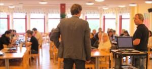 Två män står framför en åhörarskara som sitter ner