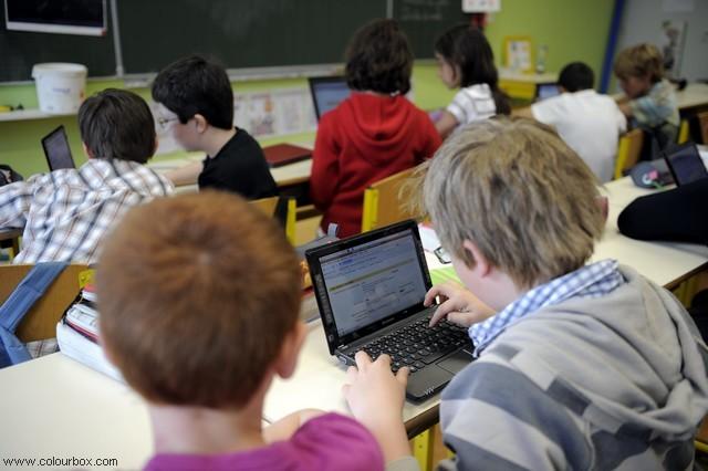 Barn sitter i skolbänkar och jobbar på sina datorer