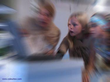 Barn ser förvånat in i dator.