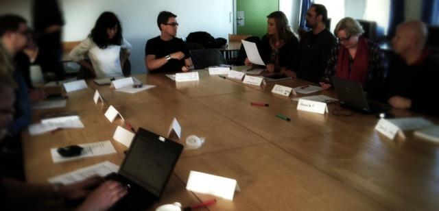 Flera personer sitter runt ett stort konferensbord och framför dem står namnskyltar