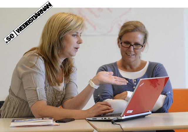Två lärare diskuterar och tittar in i en datorskärm
