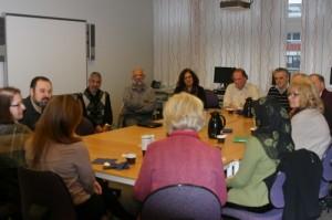 Många personer sitter runt ett konferensbord.
