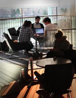 Studenter sitter vid runda bord och studerar