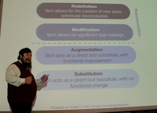 Man föreläser framför projicerad presentation
