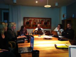 Sex personer sitter runt ett konferensbord.