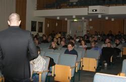 Hans Rehnman tittar ut över föreläsningssal med publik.