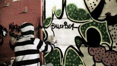 Person skriver med sprayburk på vägg.