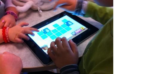 Barnhänder testar att trycka på läsplatta.
