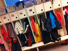 Barns kläder hänger i fack i kapprum på förskola.