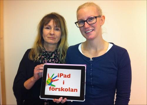 """Två kvinnor håller upp en läsplatta där det står """"Ipad i förskola""""."""