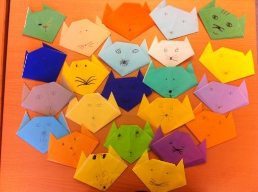 Flera färgglada katthuvuden vikta utav papper.