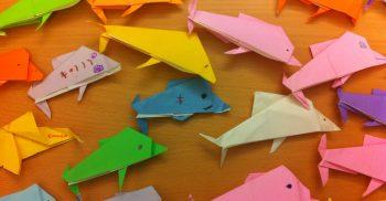 Flera färgglada delfiner vikta utav papper.