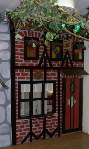 Hemmabyggd kuliss som visar ett café med hängande trädgren.