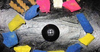 Öga bildas av knapp, makaroner och annat material.