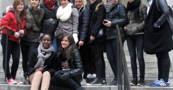 Elva ungdomar står i en stor stentrappa.