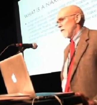 Föreläsande man står framför projicerad presentation.