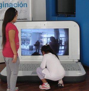 Två barn provar att skriva på en dator som är lika stor som de själva.