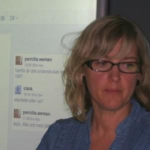 Kvinna står framför projicerad presentation.