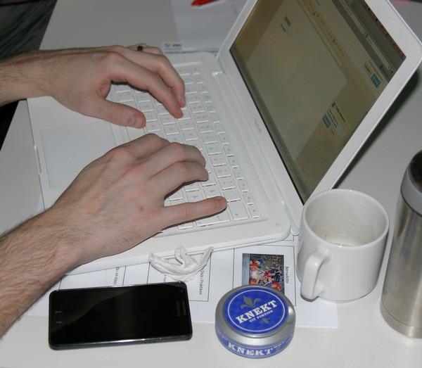Händer skriver på en vit macbook, vid sidan ligger mobiltelefon, kaffekopp och en snusdosa.