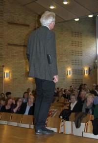 Man står på scen och föreläser för publik.