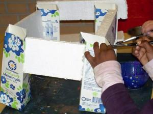 Barnhänder skapar byggnad med mjölkkartonger och frigolit.