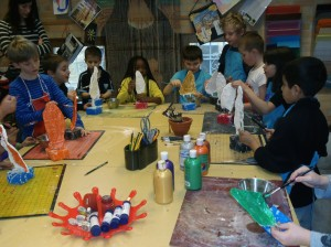 Barn skapar i atelje full av olika material.