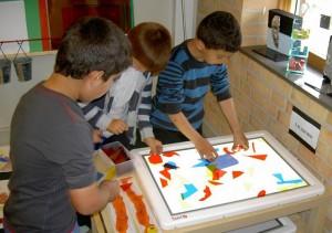 Barn skapar figurer ståendes vid ett ljusbord.