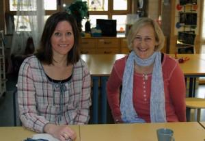 Två kvinnor sitter i skolbänk och ler.