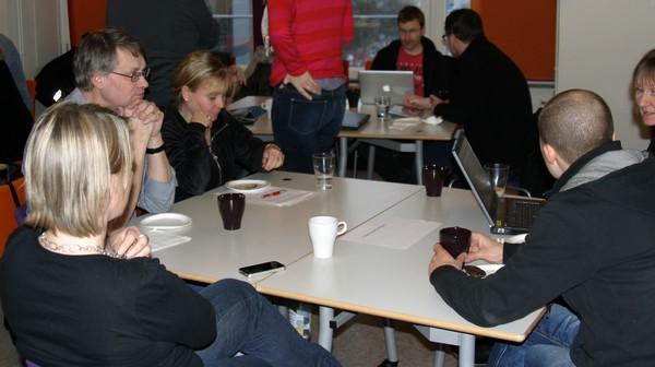 Pedagoger sitter och diskuterar runt bord.