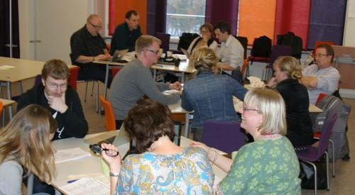 Pedagoger sitter runt bord och diskuterar.