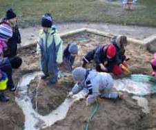 Barn lekar i sandlåda där de har byggt en kanal för vatten.