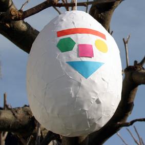 Vitt påskägg med Pedagog Malmös logotype hänger i ett träd.