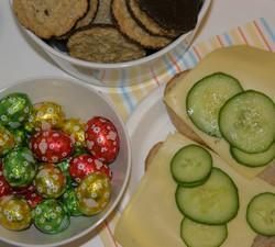 Kakor, godispåskägg och ostmackor med gurka står framdukat på ett bord.