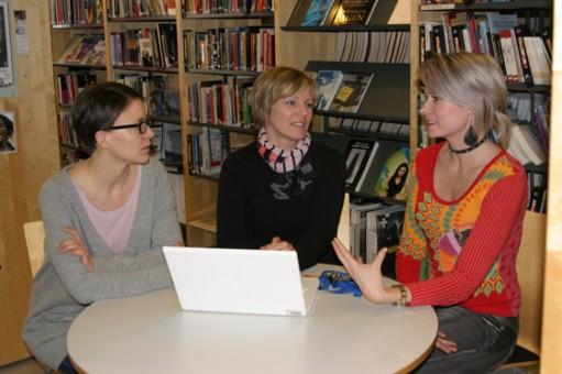 Tre kvinnor sitter i bibliotek och samtalar kring runt bord.
