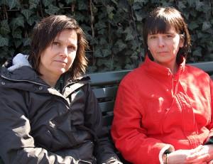 Två kvinnor sitter på bänk.