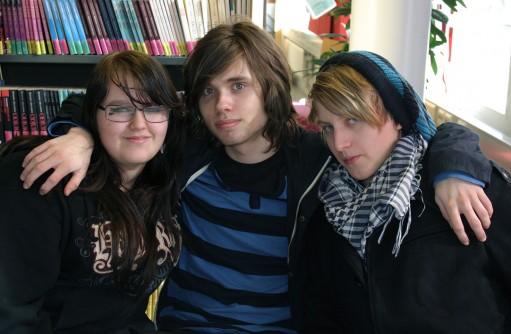 Tre elever håller om varandra.