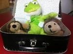 Tre små gosedjur i resväska.
