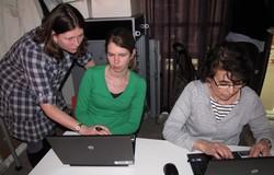 Två kvinnor sitter vid dator och en står bakom dem och förklarar och visar.