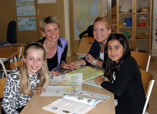 Pedagog och tre elever läser bok tillsammans.