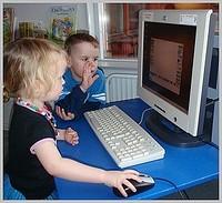 Två små barn sitter vid stationär dator med handen på datorns mus.