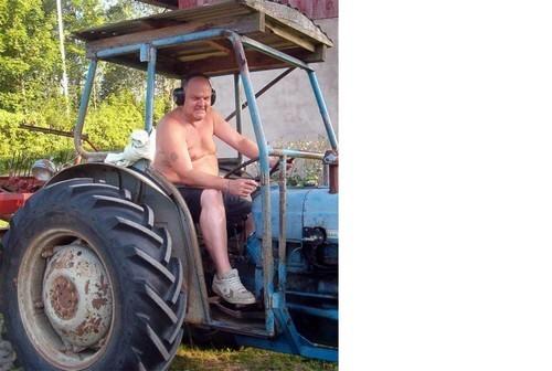 Man sitter i förarsätet på traktor.