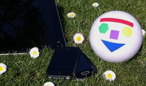 Vit boll med Pedagog Malmös logotype ligger bredvid två mobiltelefoner.