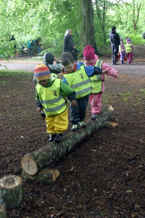Tre förskolebarn balanserar på stock.