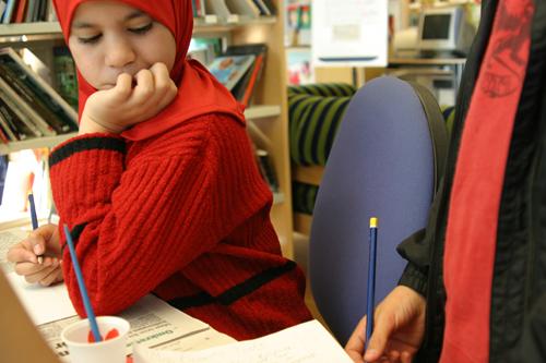 Elev håller i penna och tittar vad den andra gör.
