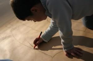 Barn ritar på stort papper på golvet.