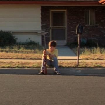 Pojke sitter på trottoar.