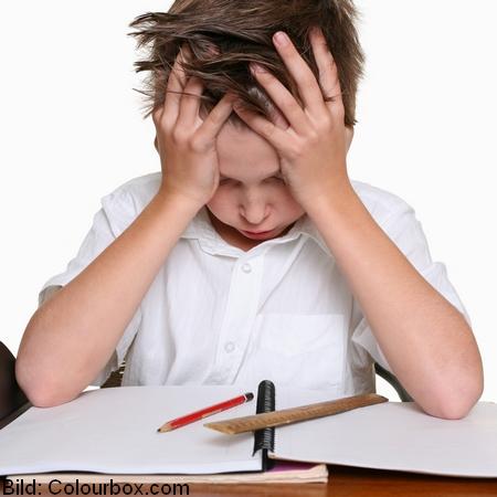 Barn håller händerna i håret och ser frustrerat ner på penna, linjal och block.